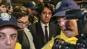 Media image of Jian Ghomeshi, in suit and tie, with journalists and cameramen visible in the foreground.